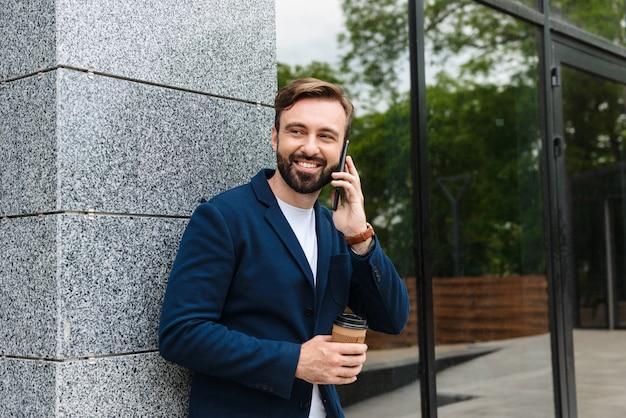 Aantrekkelijke glimlachende jonge bebaarde man met een jas die op een mobiele telefoon praat terwijl hij buiten in de stad staat en afhaalkoffie drinkt