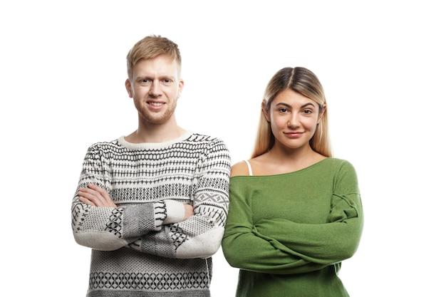 Aantrekkelijke glimlachende jonge bebaarde mannelijke en blonde vrouw die stijlvolle truien dragen die naast elkaar staan met gekruiste armen, hun blikken die vertrouwen uiten. mensen, levensstijl en relaties