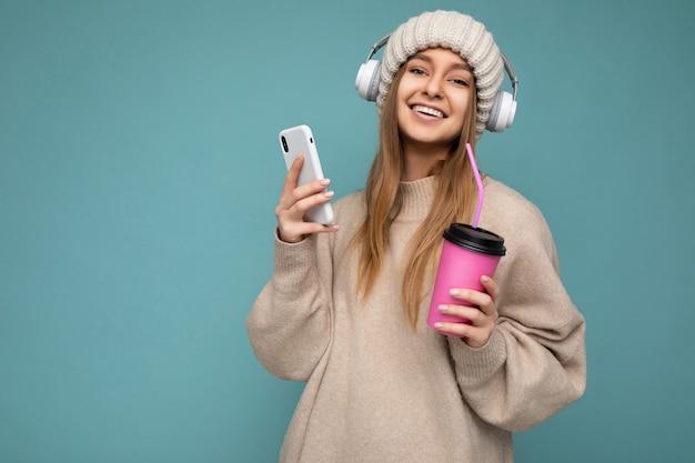 Aantrekkelijke glimlachende jonge blonde vrouw die beige sweater en beige geïsoleerde hoeden witte hoofdtelefoons draagt