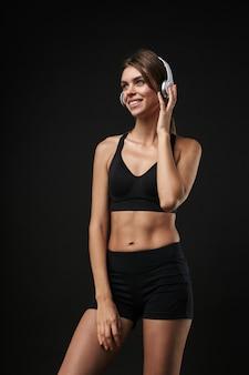 Aantrekkelijke glimlachende jonge gezonde fitnessvrouw die een sportbeha en korte broek draagt, geïsoleerd op zwarte achtergrond, luisterend naar muziek met een koptelefoon