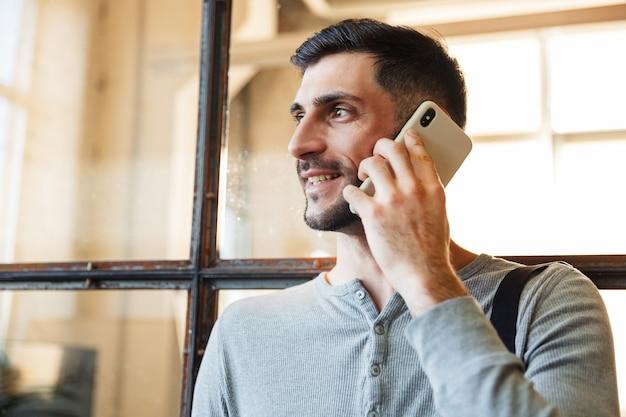Aantrekkelijke glimlachende jonge man die in de hub staat en op mobiele telefoon praat