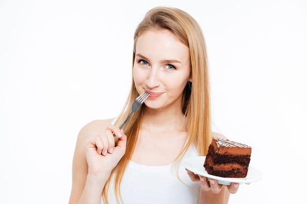 Aantrekkelijke glimlachende jonge vrouw die een stuk chocoladetaart eet op een witte achtergrond