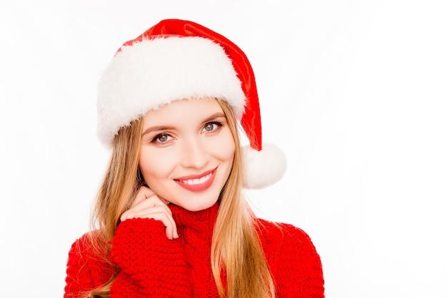 Aantrekkelijke glimlachende jonge vrouw die rode santahoed draagt