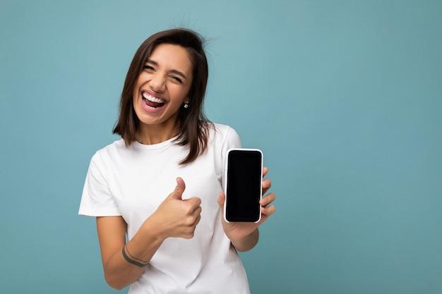 Aantrekkelijke glimlachende jonge vrouw knap dragend witte t-shirt status geïsoleerd op blauw