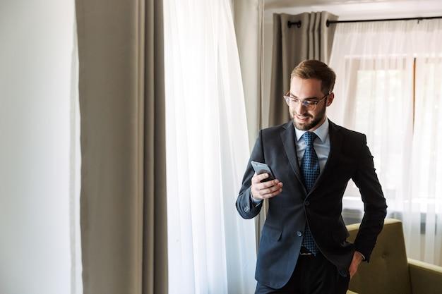 Aantrekkelijke glimlachende jonge zakenman die een pak draagt dat in de hotelkamer staat en mobiele telefoon gebruikt