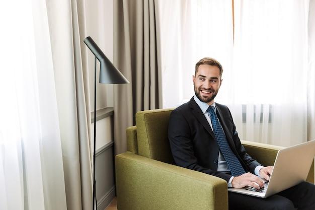 Aantrekkelijke glimlachende jonge zakenman met een pak zittend in een stoel in de hotelkamer, werkend op een laptopcomputer