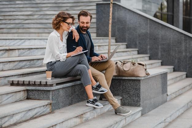 Aantrekkelijke glimlachende man en vrouw praten zittend op trappen in het stadscentrum, aantekeningen maken