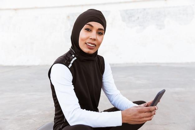 Aantrekkelijke glimlachende moslimsportvrouw die hijab buitenshuis draagt, op een fitnessmat zit, mobiele telefoon gebruikt