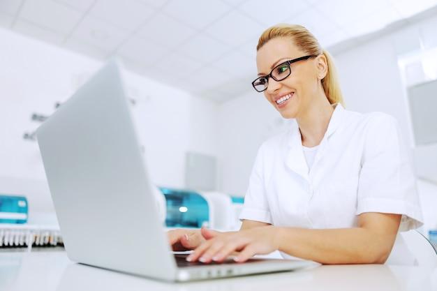 Aantrekkelijke glimlachende positieve blonde laboratoriumassistent zit in laboratorium en verwerking van gegevens.