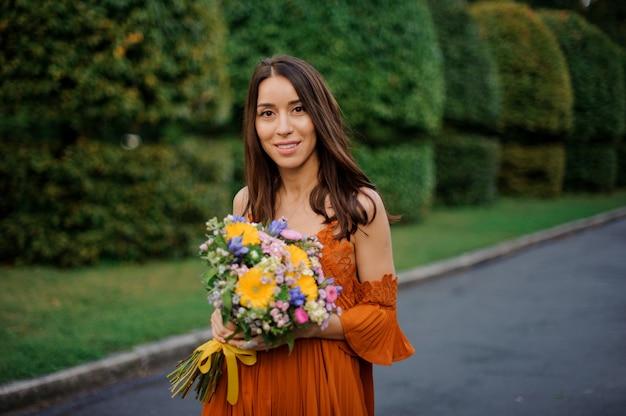 Aantrekkelijke glimlachende vrouw die in oranje kleding een boeket van bloemen houdt