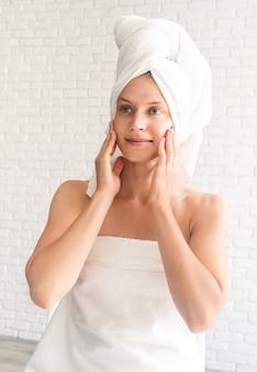 Aantrekkelijke glimlachende vrouw die kuuroordprocedures doet die de spiegel bekijken. gezichtsreiniging concept.