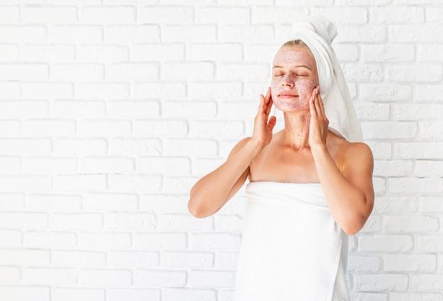 Aantrekkelijke glimlachende vrouw schrobt op haar huid toe te passen. gezichtsreiniging concept.