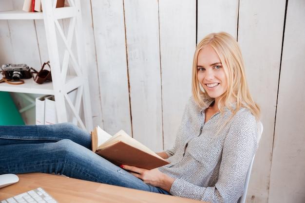 Aantrekkelijke glimlachende zakenvrouw die een boek leest terwijl ze op de werkplek op kantoor zit