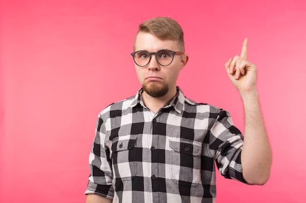 Aantrekkelijke grappige jonge man met bril en geruite overhemd die met zijn geïsoleerde vinger benadrukt
