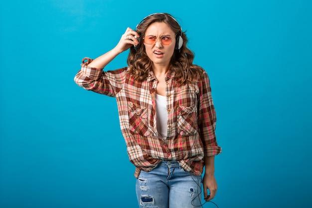 Aantrekkelijke grappige vrouw met verbaasde verdachte gezichtsuitdrukking op zoek opzij luisteren naar muziek in koptelefoon in geruit overhemd en spijkerbroek geïsoleerd op blauwe studio achtergrond