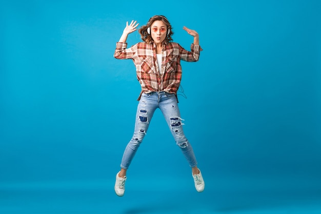 Aantrekkelijke grappige vrouw springen met gekke gezichtsuitdrukking luisteren naar muziek in koptelefoon in geruit overhemd en spijkerbroek geïsoleerd op blauwe studio achtergrond