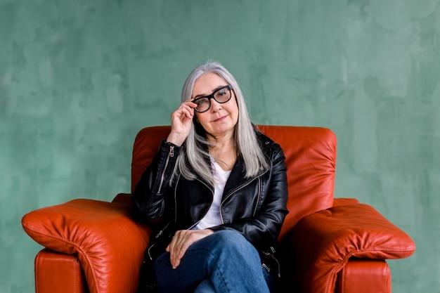 Aantrekkelijke grijze haren dame in zwart lederen jas en modieuze bril, zittend in rode fauteuil op groene achtergrond, camera kijken met een glimlach