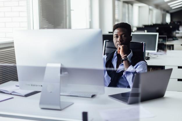 Aantrekkelijke hardwerkende jonge afro-amerikaanse kantoormedewerker zit aan de balie voor opengeklapte laptop pc en maakt aantekeningen.