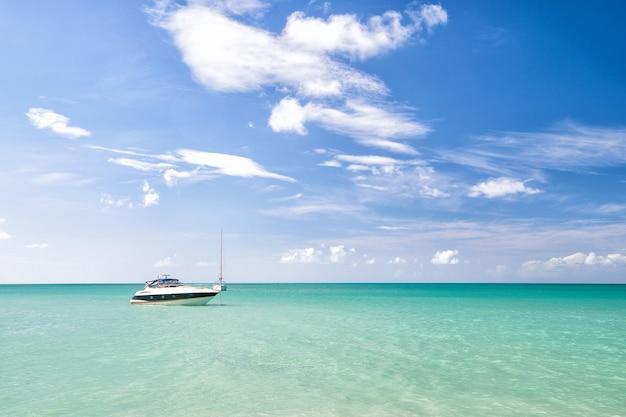 Aantrekkelijke heldere weergave van exotische kleurrijke prachtige mariene strand van antigua st. johns met boot op blauw water en lucht met kleine wolken bij zonnig weer buiten op natuurlijke achtergrond, horizontale foto