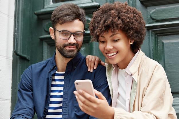 Aantrekkelijke hipster en zijn donkere vriendin kijken naar grappige video online