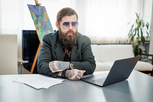 Aantrekkelijke hipster man met tatoeages in pak poses zittend aan tafel met een laptop in modern appartement. werken op afstand en huishoudelijke levensstijl.