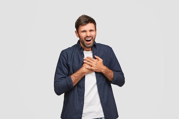 Aantrekkelijke hipster met positieve uitdrukking lacht positief, houdt beide handpalmen op de borst