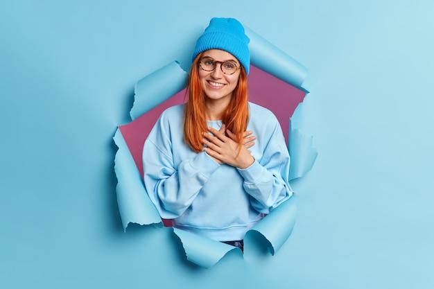 Aantrekkelijke hipster vrouw met rood haar tedere glimlach drukt handen naar hart maakt dankbaarheidsgebaar, breekt door papier gat