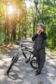 Aantrekkelijke hogere aziatische vrouw met fiets in park