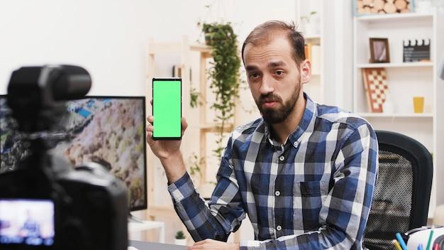 Aantrekkelijke influencer-opnamebeoordeling van telefoon met groen scherm. beroemde vloggers.