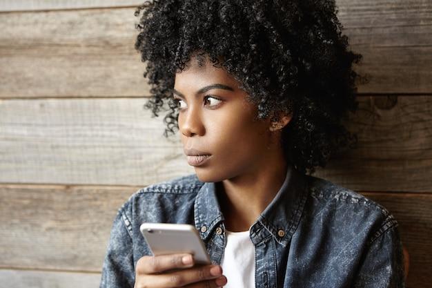 Aantrekkelijke jonge afrikaanse vrouw die fotobewerkingstoepassingen op mobiele telefoon gebruikt