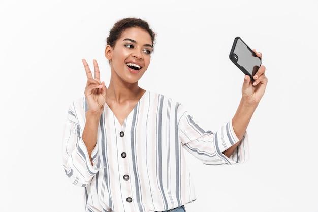Aantrekkelijke jonge afrikaanse vrouw die vrijetijdskleding draagt die geïsoleerd over een witte muur staat, een selfie neemt en vrede toont