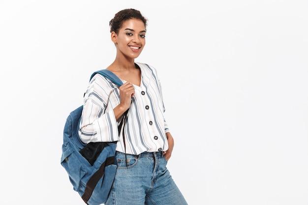Aantrekkelijke jonge afrikaanse vrouw die vrijetijdskleding draagt die geïsoleerd over een witte muur staat en een rugzak draagt