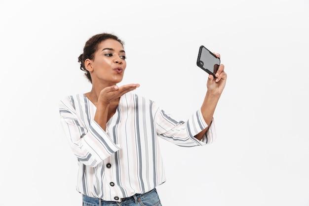 Aantrekkelijke jonge afrikaanse vrouw die vrijetijdskleding draagt, geïsoleerd over een witte muur staat, een selfie neemt, kus verzendt