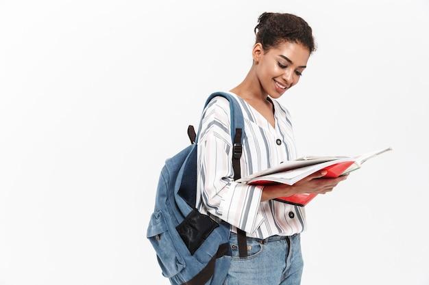 Aantrekkelijke jonge afrikaanse vrouw die vrijetijdskleding draagt, geïsoleerd over een witte muur staat, rugzak draagt, leerboek vasthoudt