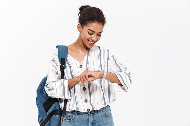 Aantrekkelijke jonge afrikaanse vrouw die vrijetijdskleding draagt, geïsoleerd over een witte muur staat, rugzak draagt, tijd controleert