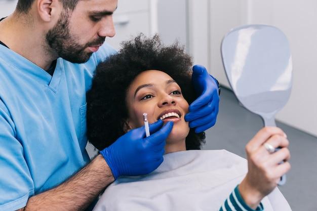 Aantrekkelijke jonge afrikaanse vrouw krijgt verjongende gezichtsinjecties. ze zit rustig in de kliniek. de deskundige schoonheidsspecialiste vult vrouwelijke rimpels op met hyaluronzuur.