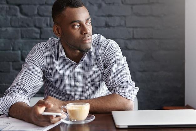 Aantrekkelijke jonge afro-amerikaanse ondernemer sms typen op slimme telefoon met doordachte en serieuze blik