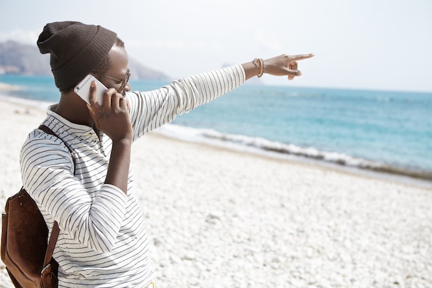 Aantrekkelijke jonge afro-amerikaanse reiziger in trendy kleding die naar iets in zee wijst terwijl hij op zijn eigentijdse mobiel praat en alleen in een vreemde stad reist. mensen en zomervakantie