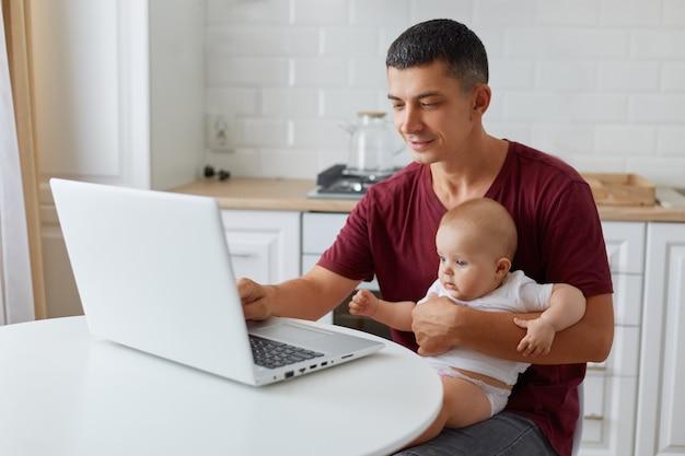 Aantrekkelijke jonge alleenstaande vader die thuis op een laptopcomputer werkt terwijl hij voor zijn dochtertje zorgt, aan tafel zit in de keuken, freelancer werkt online, binnenschot.