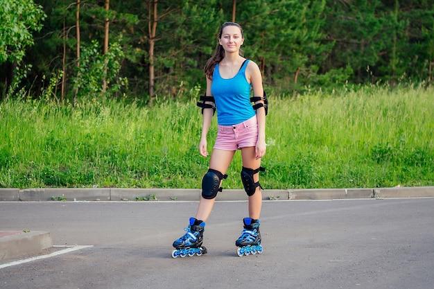 Aantrekkelijke jonge atletische slanke brunette vrouw in roze korte broek en blauwe top met bescherming elleboogbeschermers en kniebeschermers op rolschaatsen in het park
