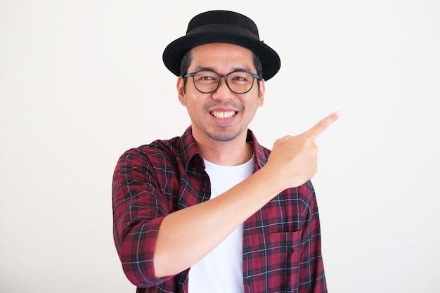 Aantrekkelijke jonge aziatische man die gelukkig lacht terwijl hij naast hem wijst