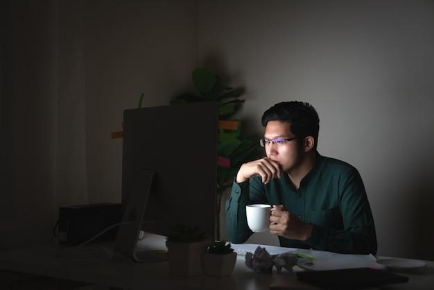 Aantrekkelijke jonge aziatische man drinken koffie zittend op tafel