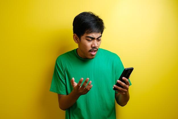 Aantrekkelijke jonge aziatische man leest sms'en chatten op zijn telefoon, slecht nieuws, droevige huilende uitdrukking tegen gele achtergrond