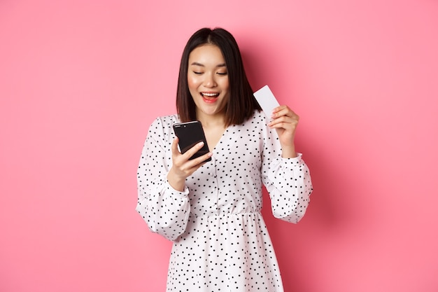 Aantrekkelijke jonge aziatische vrouw bestelt online met creditcard en mobiele telefoon en maakt internetaankopen...