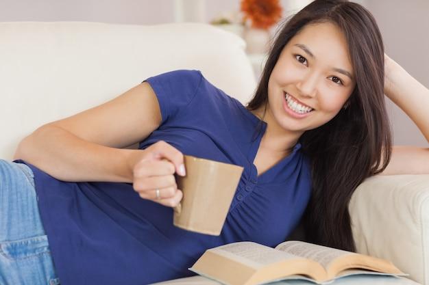 Aantrekkelijke jonge aziatische vrouw die op de bank ligt die een roman leest en hete drank drinkt