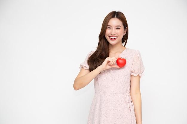 Aantrekkelijke jonge aziatische vrouw die rood liefdehart houdt dat op witte muur wordt geïsoleerd