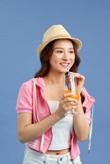 Aantrekkelijke jonge aziatische vrouw die vruchtensap drinkt over blauwe achtergrond.