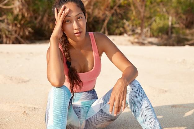 Aantrekkelijke jonge aziatische vrouw gekleed in t-shirt en beenkappen, heeft rust na het trainen op zandstrand