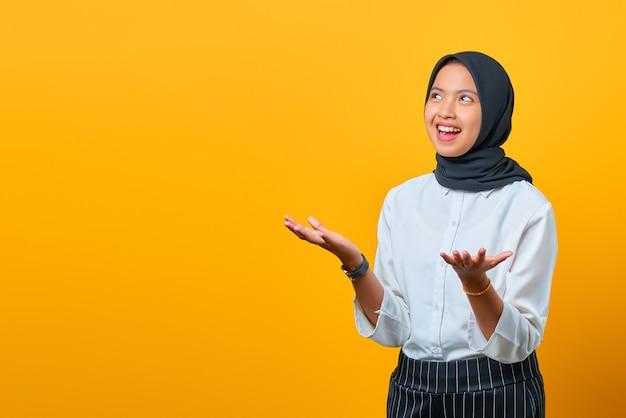 Aantrekkelijke jonge aziatische vrouw met lachgezicht en opgeheven hand geïsoleerd over gele achtergrond