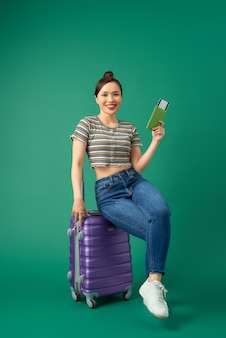 Aantrekkelijke jonge aziatische vrouw zittend op koffer en bedrijf paspoort, ticketvlucht over groen.